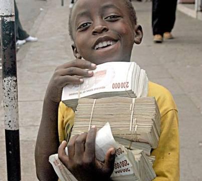 Niño de Zimbabwe cargando billetes sin valor debido a la hiperinflación.